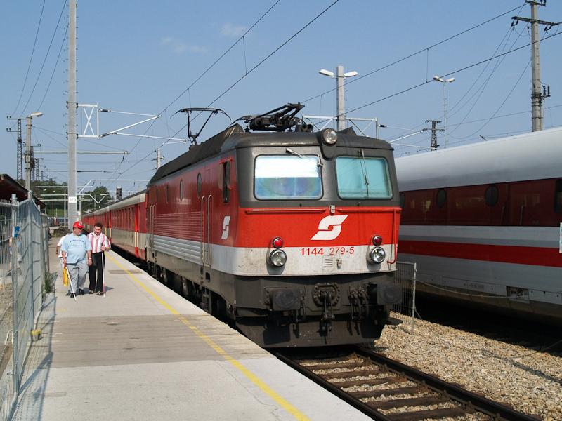 The ÖBB 1144 279-5 seen hauling four Jaffa-livery Schlierenwagen at St. Pölten Hauptbahnhof photo