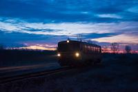 A MÁV-START 117 169 pályaszámú Bézé-motorkocsi döcög a 103-as, Karcag-Tiszafüred vicinálison Kunmadaras és Pusztakettős között napkeltekor