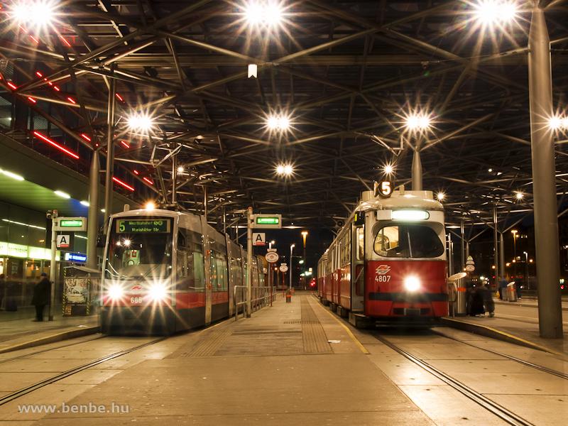 A 685 pályaszámú ULF és a 4807 pályaszámú E1 villamoskocsi Wien Pratersternben, az állomás előtti téren található fedett megállóban fotó