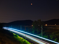A FLIRT trainset at Biatorb�gy station during a lunar eclipse
