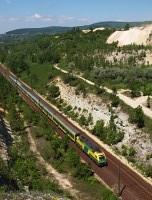A GYSEV/Raaberbahn 1047 502-8 pályaszámú Taurus mozdonya egy Sopron-Budapest, tiszta zöld-sárga kocsis gyorsvonattal Alsógalla és Szárliget között, a bevágásnál