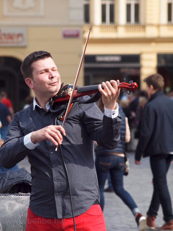 A violinists plays with big photo