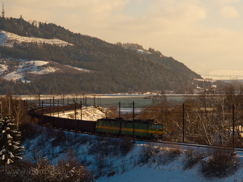 A freight train hauled by a ŽSSKC class 131 electric locomotive seen near the reservoir Liptovská Mara between Liptovská Teplá and Liptovské Vlachy photo