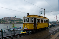 The BKV woodframe historic tram number 2806 at Vigadó tér, with the Buda Castle in the background