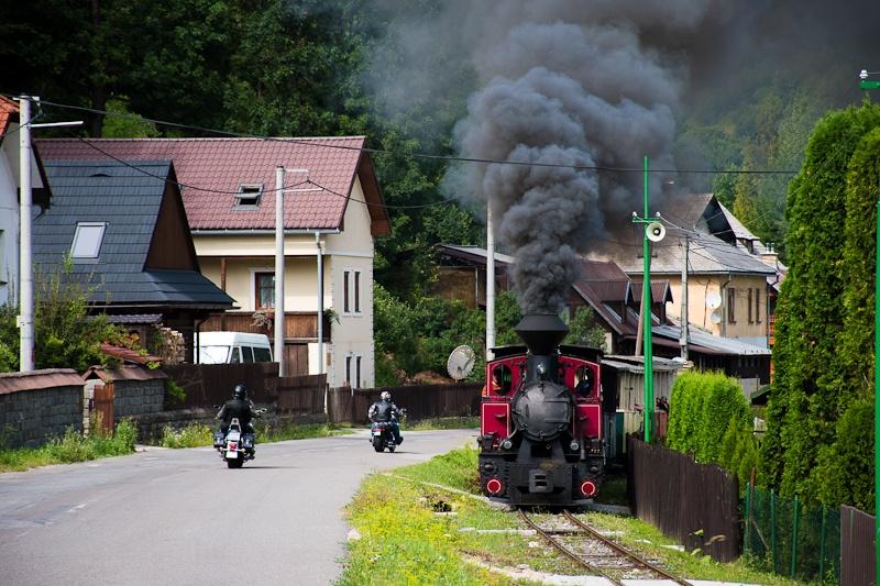 A Čiernohronská Lesná Železnica 764 407 Feketebalog és Vydrovo Skanzen között az utcán kanyarog a kisvasút fotó