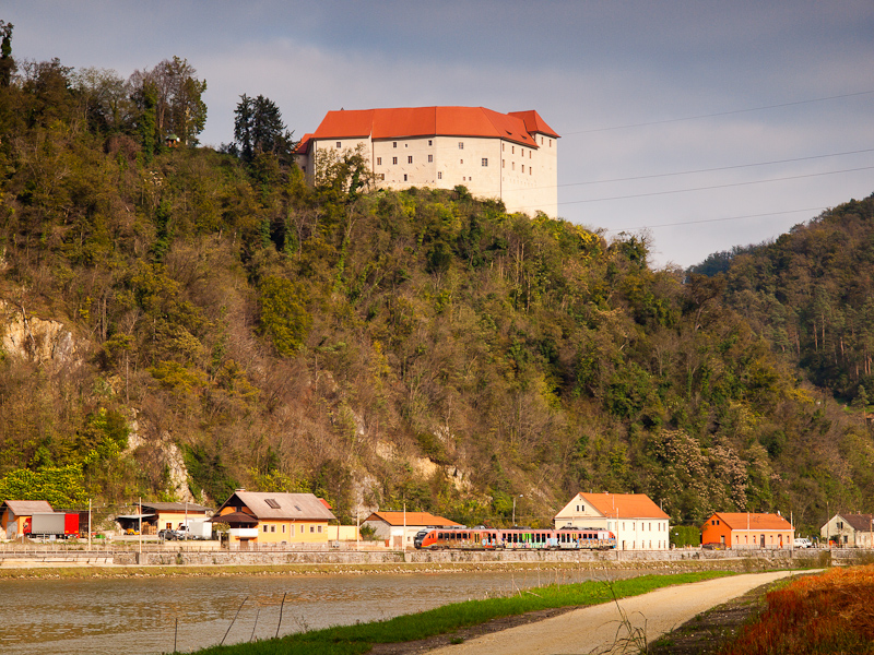 A Slovenian class 312 - 100 electric Desiro trainset seen between Brestanica and Blanca with Grad Rajhenburg castle in the background  photo