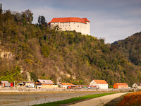 A Slovenian class 312 - 100 electric Desiro trainset seen between Brestanica and Blanca with Grad Rajhenburg castle in the background