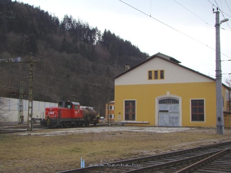A 2068 009-6 pályaszámú mozdony a javítóműhely egyik csarnoka mellett, egy tartálykocsi betolása közben fotó