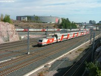 An InterCity2 train with an Sr2 type locomotive is running to Turku near Ilmala with a Pendolino exiting Ilmala depot in the background