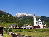 The RhB Ge 4/6 353 with the Alpine Classic Pullman Express at the classical photo site with the church at Trun