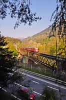 Az RhB Be 4/4 514-es Rhäzünsbe tartó S-Bahn vonattal a Reichenau-Tamins melletti Hátsó-Rajna-hídon