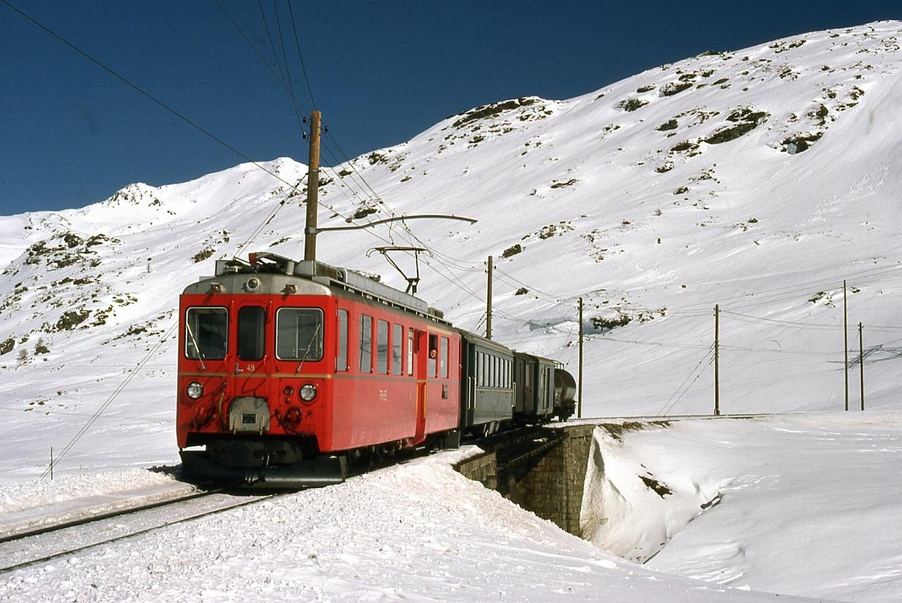 A TW II (ABe 4/4 II) sorozatú, 49 pályaszámú motorkocsi, még régi kialakítása szerint, egy vegyesvonattal a Bernina-hágón Ospizio Bernina és (akkor még) Bernina Diavolezza között fotó