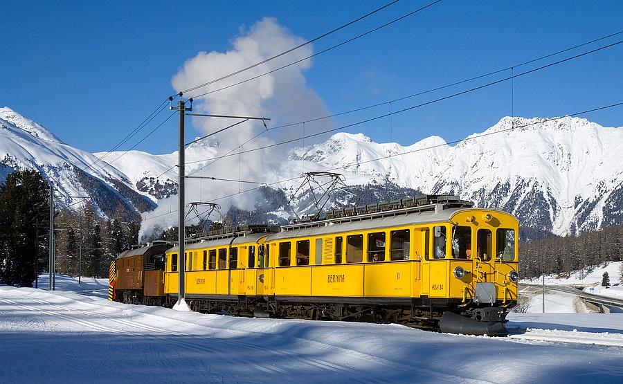 A Berninabahn ABe 4/4 I  34 pályaszámú nosztalgia-motorkocsija az eredeti festési terv szerint fényezve a BB gőzhómarójával Pontresina/Puntraschigna és Punt Muragl Staz között 2010. január 16-án fotó