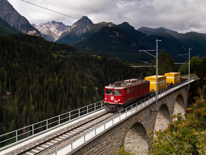 Az RhB Ge 6/6 II  704, szép, kereklámpás tehervonati villanymozdony Ftan-Baraigla és Scuol-Tarasp között a 91,1 méter hosszú, 16 méteres ívekből álló Val Lumes-Viadukton halad át rövidke tehervonatával - a háttérben Tarasp vára fotó
