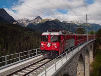 Az RhB Ge 4/4 II  633 pályaszámú villanymozdonya Ftan-Baraigla és Scuol-Tarasp között a 91,1 méter hosszú, 16 méteres ívekből álló Val Lumes-Viadukton halad át - a háttérben Tarasp vára