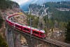 The Rhätische Bahn ABe 8/12 3509 seen between Filisur and Alvaneu at the Schmittentobel-Viadukt extended by Swiss Post containers as a PmG (Personenzug mit Güterbefohrderung)