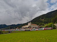 The RhB Ge 4/4<sup>III</sup> 645 is pulling the Glacier-Express panoramicout of Disentis/Must�r station with the abbey in the background