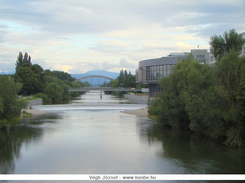 A Traisen hídjáról nézve látszanak a hegyek, ahonnan a folyó is érkezik, és amelyik irányba halad a Traisentalbahn vonala is. Jobbra pedig a kormányzati negyed épületei láthatók a parton. fotó